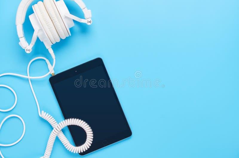 Τοπ άποψη επάνω στις συσκευές στο μπλε υπόβαθρο, τη σύνθεση των άσπρων ακουστικών και την ταμπλέτα στοκ φωτογραφία με δικαίωμα ελεύθερης χρήσης