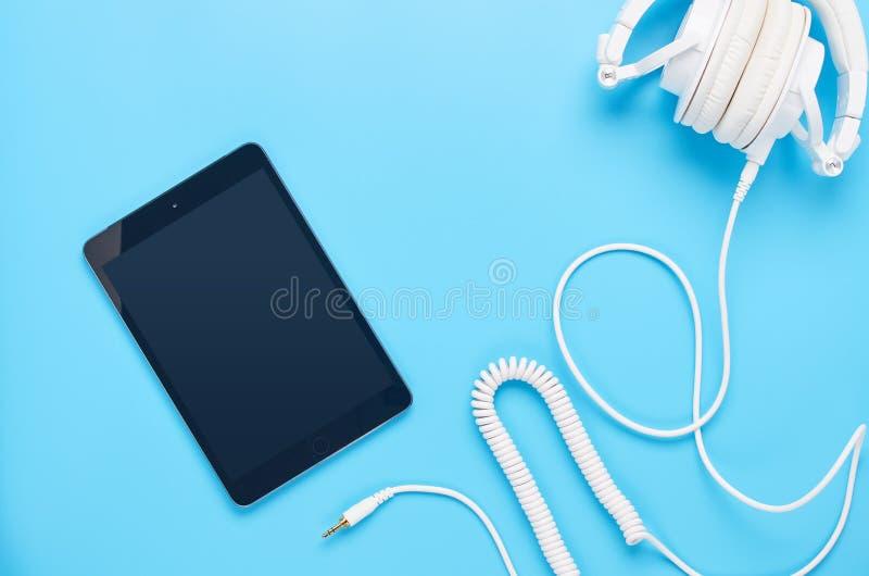 Τοπ άποψη επάνω στις συσκευές στο μπλε υπόβαθρο, τη σύνθεση των άσπρων ακουστικών και την ταμπλέτα στοκ εικόνες με δικαίωμα ελεύθερης χρήσης