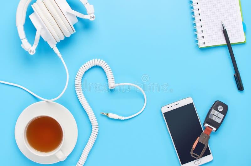 Τοπ άποψη επάνω στις συσκευές στο μπλε υπόβαθρο, τη σύνθεση των άσπρων ακουστικών, το τηλέφωνο, την ταμπλέτα, το γυαλί με ένα ποτ στοκ φωτογραφία με δικαίωμα ελεύθερης χρήσης