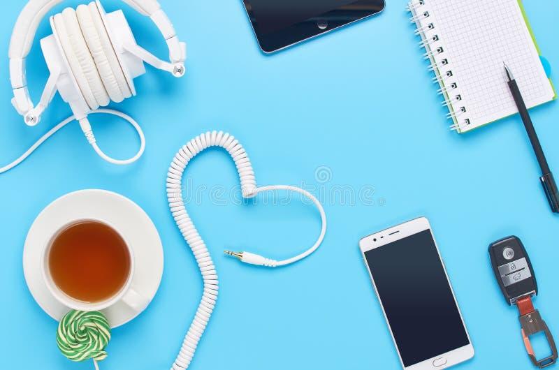 Τοπ άποψη επάνω στις συσκευές στο μπλε υπόβαθρο, τη σύνθεση των άσπρων ακουστικών, το τηλέφωνο, την ταμπλέτα, το γυαλί με ένα ποτ στοκ εικόνες με δικαίωμα ελεύθερης χρήσης