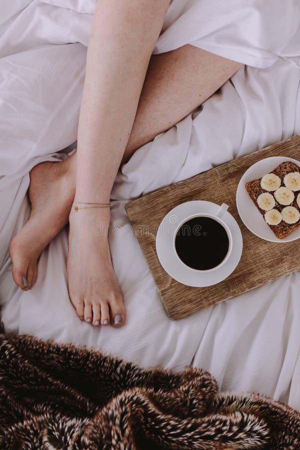 Τοπ άποψη μιας γυναίκας στο κρεβάτι με το πρόγευμα στοκ εικόνες