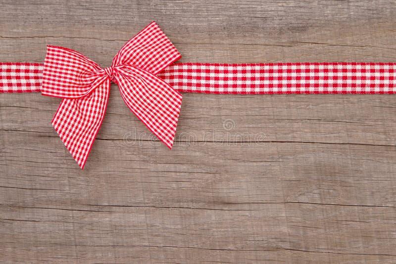 Τοπ άποψη μιας κόκκινης ελεγχμένης διακόσμησης κορδελλών στο ξύλινο υπόβαθρο στοκ φωτογραφία με δικαίωμα ελεύθερης χρήσης
