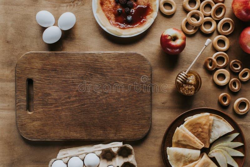 τοπ άποψη νόστιμα σπιτικά bagels αυγών τηγανιτών ξύλινα τέμνοντα μέλι και και μήλων πινάκων κιβωτίων αυγών στοκ φωτογραφία με δικαίωμα ελεύθερης χρήσης