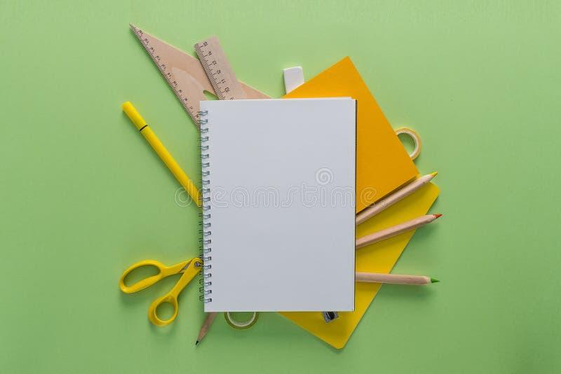 Τοπ άποψη πέρα από σημειωματάρια, μολύβια, ψαλίδι, κυβερνήτες, ταινίες και γόμα σε ένα πράσινο υπόβαθρο πίσω σχολείο έννοιας Παρά στοκ φωτογραφίες