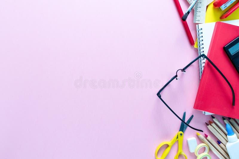 Τοπ άποψη πέρα από σημειωματάρια, χρώματα, μολύβια, ψαλίδι, γυαλιά, υπολογιστής, κόλλα και γόμα σε ένα ρόδινο υπόβαθρο Πίσω στο σ στοκ εικόνα με δικαίωμα ελεύθερης χρήσης