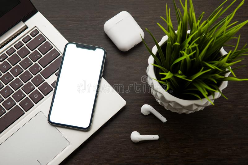 Τοπ άποψη σχετικά με ένα πληκτρολόγιο lap-top smartphone και ασύρματα ακουστικά σε έναν καφετή πίνακα δίπλα σε έναν houseplant στοκ φωτογραφία