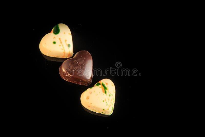 Τοπ άποψη σχετικά με καρδιά-διαμορφωμένες τις σειρά άσπρες και μαύρες καραμέλες σοκολάτας στοκ εικόνες