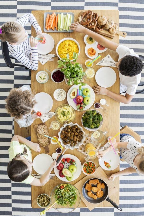 Τοπ άποψη σχετικά με τα παιδιά που τρώνε τα υγιή τρόφιμα στον πίνακα κατά τη διάρκεια του birthda στοκ φωτογραφία