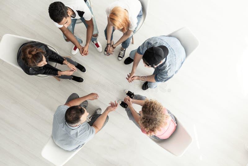 Τοπ άποψη σχετικά με την ομάδα εφήβων που κάθονται σε έναν κύκλο κατά τη διάρκεια του προξένου στοκ εικόνα