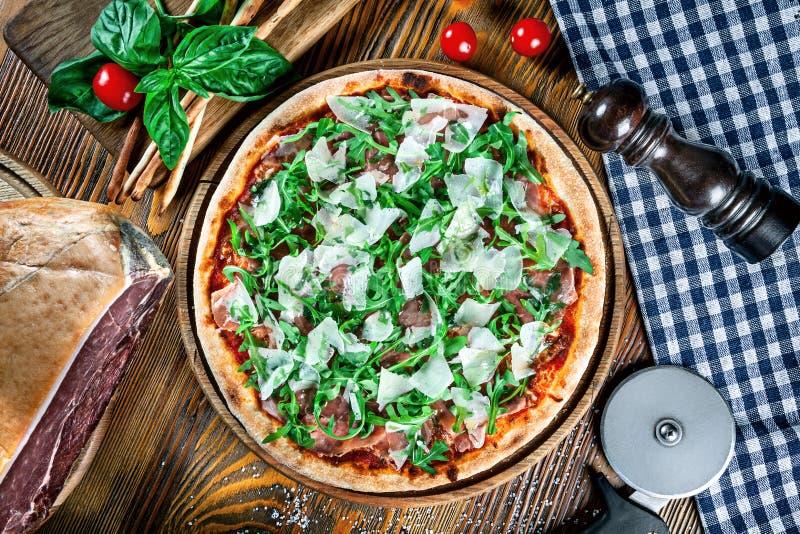 Τοπ άποψη σχετικά με τη σπιτική ιταλική πίτσα με το prosciutto και το arugula στοκ φωτογραφία με δικαίωμα ελεύθερης χρήσης