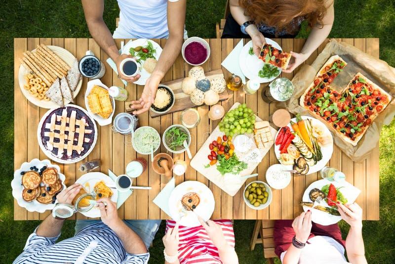 Τοπ άποψη σχετικά με τους ανθρώπους που τρώνε το μεσημεριανό γεύμα στον πίνακα κήπων κατά τη διάρκεια του κόμματος στοκ φωτογραφίες