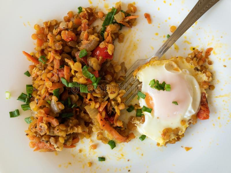 Τοπ άποψη σχετικά με το πιάτο με το τηγανισμένο αυγό, κόκκινη φακή που ψήνεται με τα λαχανικά στοκ φωτογραφίες