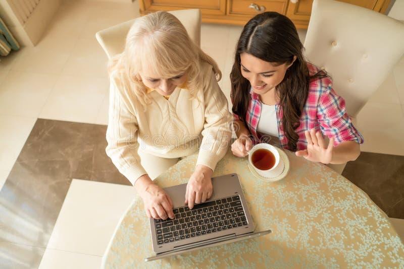 Τοπ άποψη της ανώτερης γυναίκας και της κόρης της που κυματίζουν στη κάμερα του lap-top στοκ φωτογραφία
