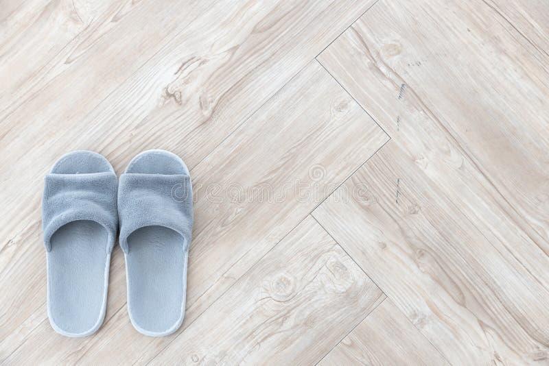 Τοπ άποψη της γκρίζας παντόφλας μαλλιού στην καφετιά ξύλινη σύσταση υποβάθρου πατωμάτων ψαροκόκκαλων στοκ εικόνες με δικαίωμα ελεύθερης χρήσης