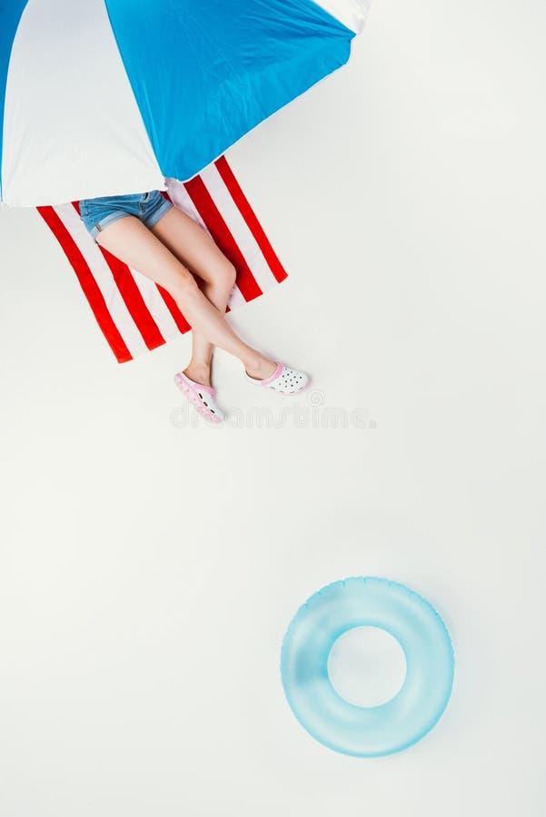 τοπ άποψη της γυναίκας που βρίσκεται στη ριγωτή πετσέτα παραλιών κάτω από την ομπρέλα παραλιών στοκ φωτογραφία με δικαίωμα ελεύθερης χρήσης