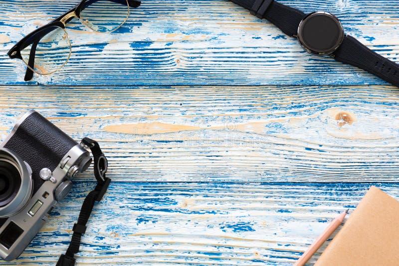Τοπ άποψη της ελάχιστης αρσενικής έννοιας ταξιδιού με τα γυαλιά, το ρολόι, τη κάμερα, το σημειωματάριο και το μολύβι στην ανοικτό στοκ εικόνα