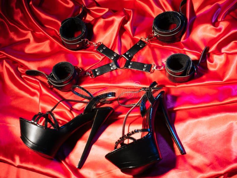 Τοπ άποψη της εξάρτησης bdsm Δουλεία και ένα ζευγάρι των μαύρων ψηλοτάκουνων παπουτσιών στο κόκκινο λινό Ενήλικα παιχνίδια φύλων  στοκ εικόνες