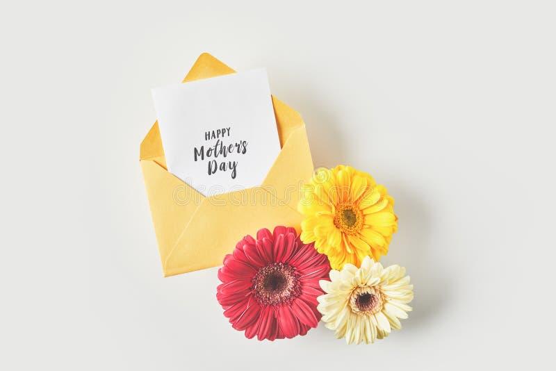 τοπ άποψη της ευτυχούς ευχετήριας κάρτας ημέρας μητέρων στο φάκελο και των όμορφων λουλουδιών gerbera στο γκρι στοκ φωτογραφία