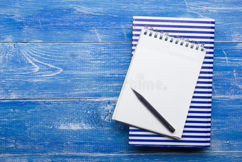 Τοπ άποψη της δημιουργικής έννοιας γραψίματος με τα μολύβια, βιβλίο, σημειωματάριο στον ξύλινο πίνακα Διάστημα αντιγράφων για το  στοκ εικόνες
