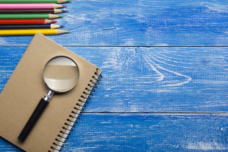 Τοπ άποψη της δημιουργικής έννοιας γραψίματος με τα μολύβια, βιβλίο, σημειωματάριο στον ξύλινο πίνακα Διάστημα αντιγράφων για το  στοκ εικόνα