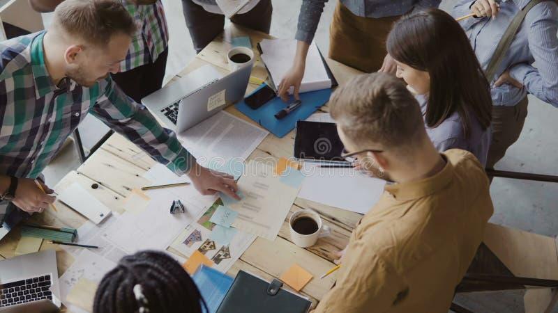 Τοπ άποψη της μικτής στάσης ομάδων ανθρώπων φυλών κοντά στον πίνακα Νέα επιχειρησιακή ομάδα που εργάζεται στο πρόγραμμα ξεκινήματ στοκ εικόνες