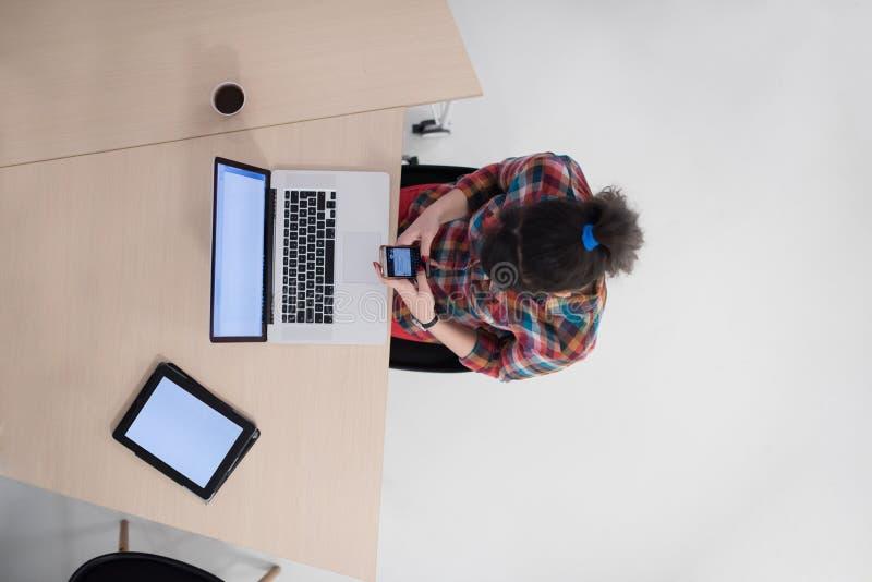 Τοπ άποψη της νέας επιχειρησιακής γυναίκας που εργάζεται στο lap-top στοκ εικόνες