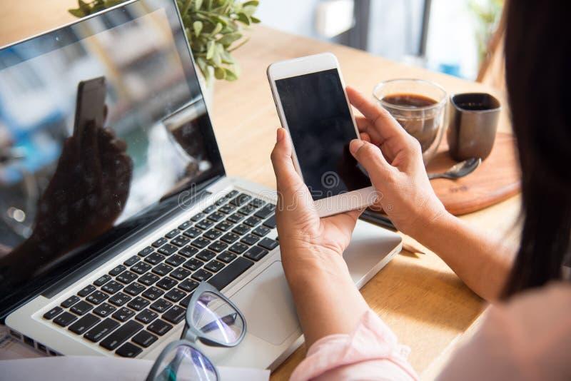 Τοπ άποψη της νέας εργαζόμενης γυναίκας χρησιμοποιώντας το lap-top και διαβάζοντας το έγγραφο ετήσια εκθέσεων στην εργασία στοκ εικόνες