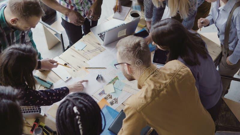 Τοπ άποψη της νέας ομάδας που εργάζεται στο νέο πρόγραμμα Ομάδα μικτών ανθρώπων φυλών που στέκονται κοντά στον πίνακα και τη συζή στοκ εικόνες