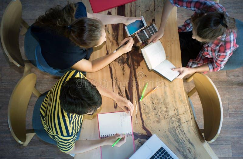 Τοπ άποψη της ομάδας συναδέλφων που εργάζονται στην ομάδα με τις εκθέσεις και το lap-top στοκ φωτογραφία με δικαίωμα ελεύθερης χρήσης