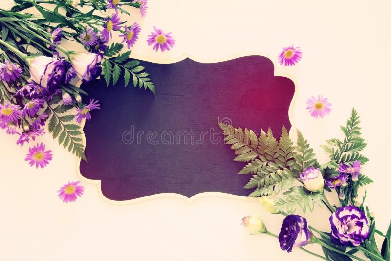 Τοπ άποψη της πορφυρής όμορφης ρύθμισης λουλουδιών και του κενού πίνακα πέρα από το άσπρο ξύλινο υπόβαθρο διάστημα αντιγράφων στοκ εικόνες