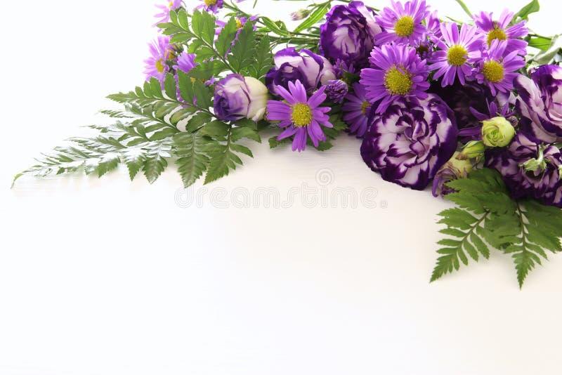 Τοπ άποψη της πορφυρής όμορφης ρύθμισης λουλουδιών στο άσπρο ξύλινο υπόβαθρο διάστημα αντιγράφων στοκ εικόνες