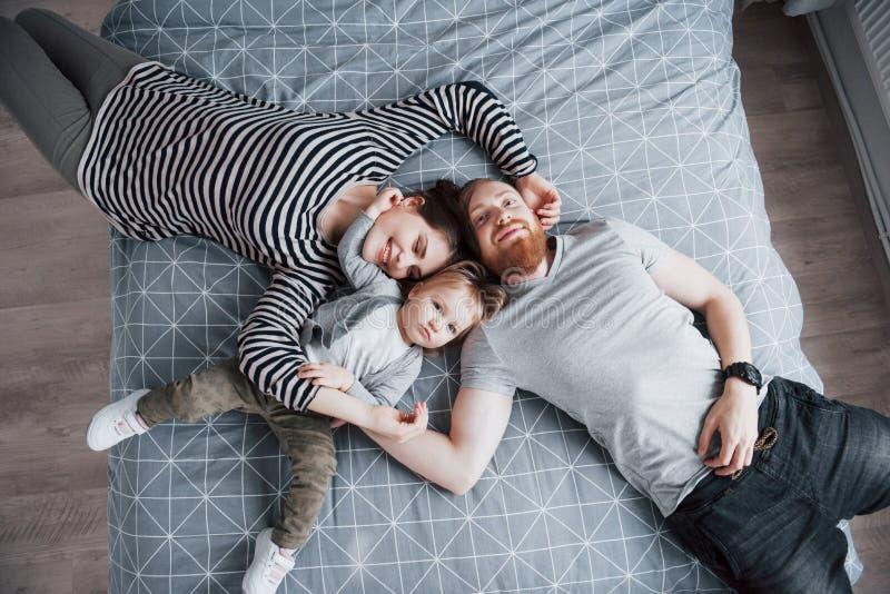 Τοπ άποψη της όμορφης νέας μητέρας, του πατέρα και της κόρης τους που εξετάζουν τη κάμερα και που χαμογελούν στο κεφάλι κρεβατιών στοκ εικόνες
