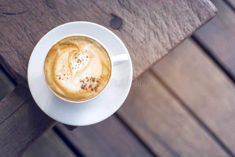 Τοπ άποψη του άσπρου φλυτζανιού του καυτού cappuccino με την τέχνη καρδιών latte στον ξύλινο πίνακα στοκ φωτογραφία με δικαίωμα ελεύθερης χρήσης
