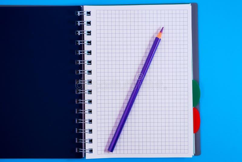 Τοπ άποψη του ανοικτού σπειροειδούς κενού σημειωματάριου με το μολύβι στο μπλε υπόβαθρο γραφείων στοκ φωτογραφία με δικαίωμα ελεύθερης χρήσης