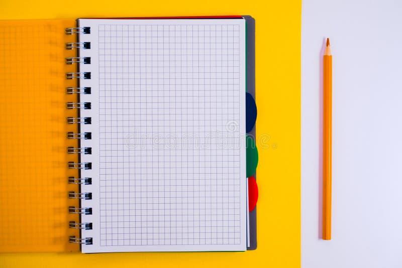 Τοπ άποψη του ανοικτού σπειροειδούς κενού σημειωματάριου με το μολύβι στο κίτρινο υπόβαθρο γραφείων στοκ εικόνες