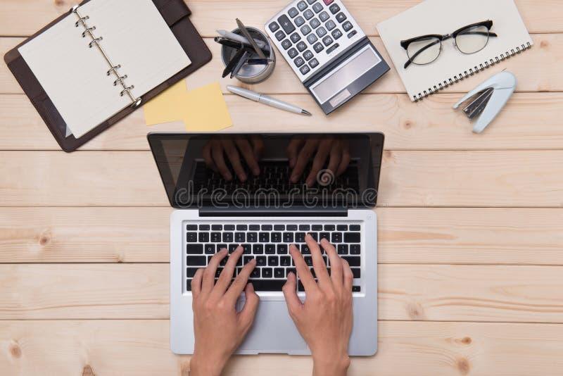 Τοπ άποψη του ατόμου που χρησιμοποιεί έναν σύγχρονο φορητό υπολογιστή στο Υπουργείο Εσωτερικών στοκ εικόνα