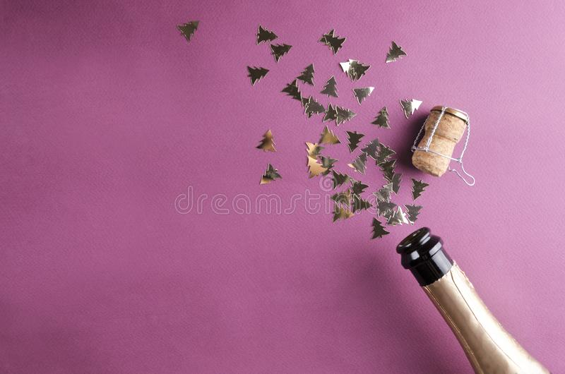 Τοπ άποψη του βουλωμένου μπουκαλιού της σαμπάνιας και του λαμπρού χρυσού κομφετί στην πορφυρή επιφάνεια στοκ εικόνες με δικαίωμα ελεύθερης χρήσης