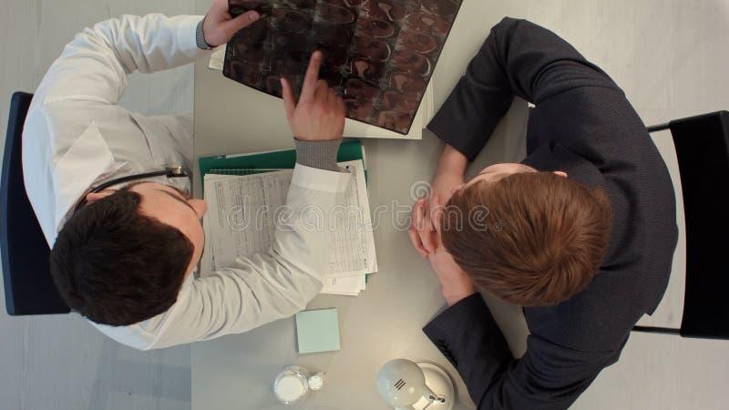 Τοπ άποψη του γιατρού που έχει τη συνομιλία με τον ασθενή του και που κρατά την ακτίνα X στο ιατρικό γραφείο στοκ εικόνα