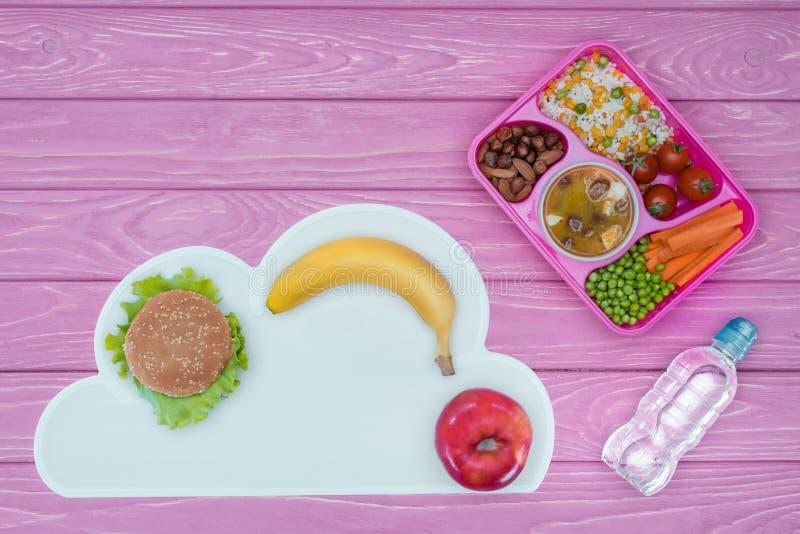 τοπ άποψη του δίσκου με το μεσημεριανό γεύμα παιδιών για το σχολείο, burger και τα φρούτα στοκ εικόνα