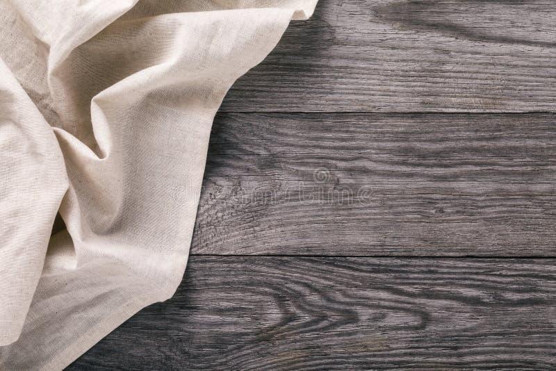 Τοπ άποψη του ελαφριού τραπεζομάντιλου στην αριστερή πλευρά του ξύλινου πίνακα στοκ φωτογραφία