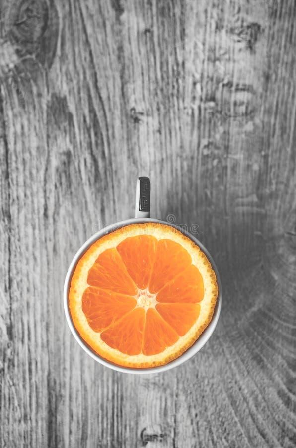 Τοπ άποψη του εύγευστου γλυκού πορτοκαλιού στο φλυτζάνι που απομονώνεται σε ένα ξύλινο β