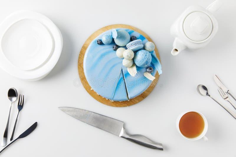 τοπ άποψη του κέικ στον τεμαχίζοντας πίνακα με το μαχαίρι, τα πιάτα και το τσάι στοκ εικόνες