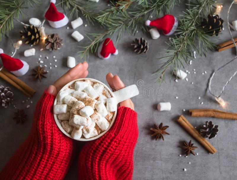 Τοπ άποψη του καυτά φλυτζανιού & marshmallows σοκολάτας στο θηλυκό χέρι που φορά το κόκκινο πουλόβερ, ενάντια στο γκρίζο θέμα υπο στοκ φωτογραφία με δικαίωμα ελεύθερης χρήσης