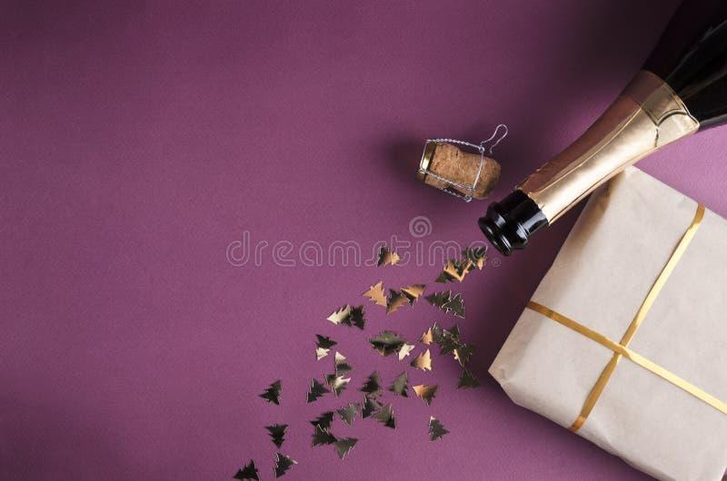 Τοπ άποψη του κιβωτίου δώρων, μπουκάλι σαμπάνιας, κομφετί στο πορφυρό υπόβαθρο στοκ φωτογραφία