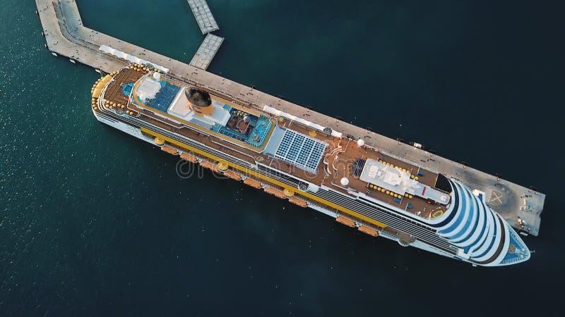 Τοπ άποψη του κρουαζιερόπλοιου κοντά στην αποβάθρα με ένα κοπάδι των πουλιών που πετούν επάνω από τη γέφυρα Απόθεμα Εναέρια άποψη στοκ φωτογραφία