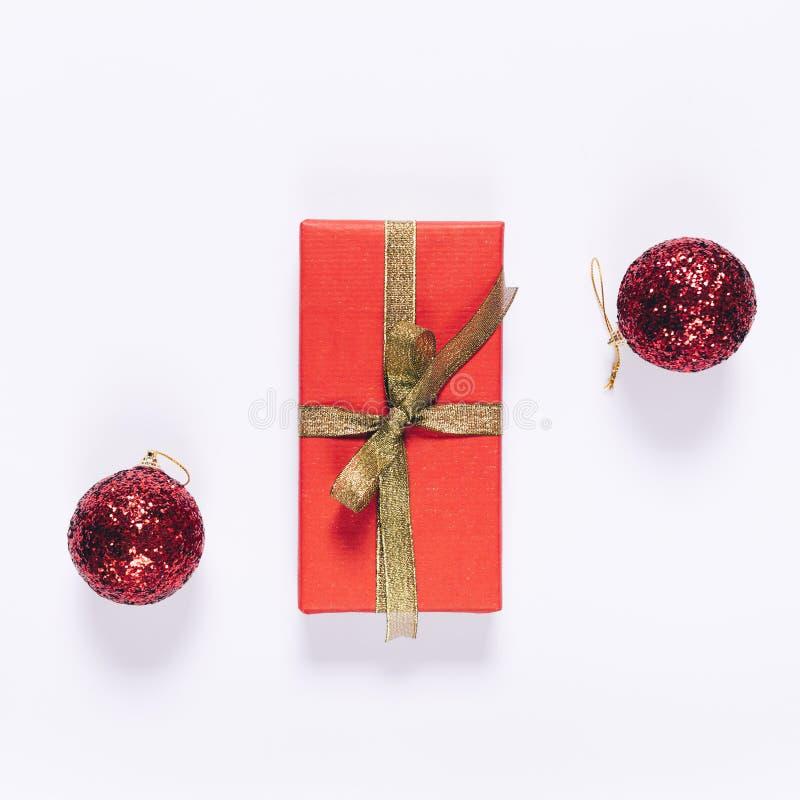 Τοπ άποψη του κόκκινου κιβωτίου δώρων με τις χρυσές σφαίρες κορδελλών και Χριστουγέννων στοκ εικόνες