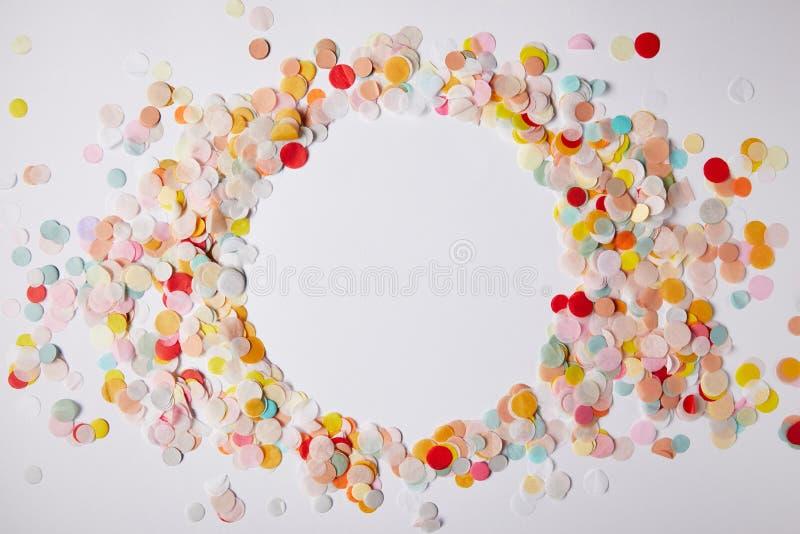 τοπ άποψη του κύκλου των χρωματισμένων κομματιών κομφετί στην άσπρη επιφάνεια στοκ φωτογραφία με δικαίωμα ελεύθερης χρήσης