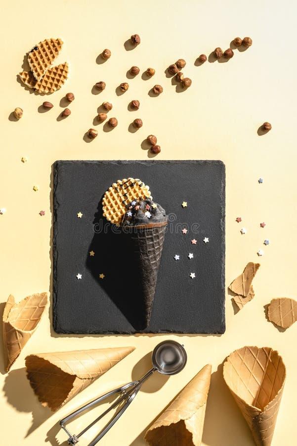 τοπ άποψη του μαύρου παγωτού σοκολάτας και των κενών κώνων παγωτού στοκ εικόνα