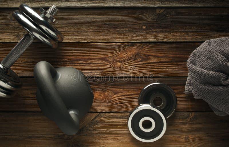 Τοπ άποψη του μαύρου σιδήρου kettlebell, του αλτήρα και της γκρίζας πετσέτας στο wo στοκ φωτογραφία με δικαίωμα ελεύθερης χρήσης