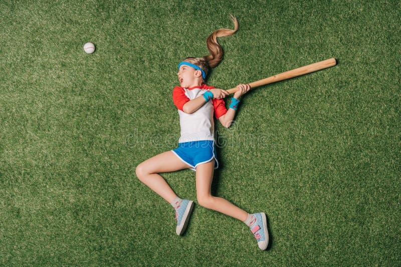 Τοπ άποψη του μικρού κοριτσιού που προσποιείται το παίζοντας μπέιζ-μπώλ στη χλόη στοκ εικόνα